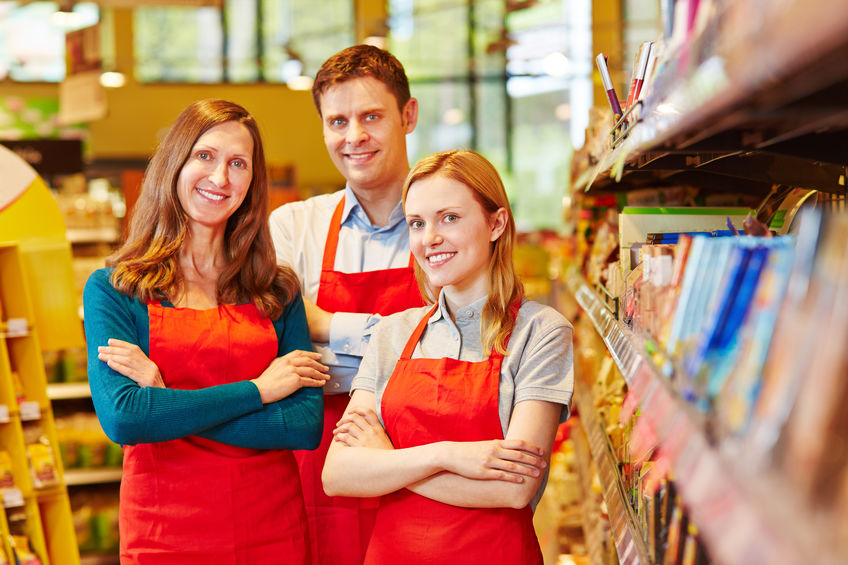 Smiling Sales Team Staff In Supermarket With Their Arms Crossed