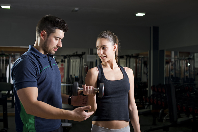 38497879 - Woman Lifting Weights At Gym Training Biceps. Personal Trainer Helps. Focus Is In Woman.low Key Image.
