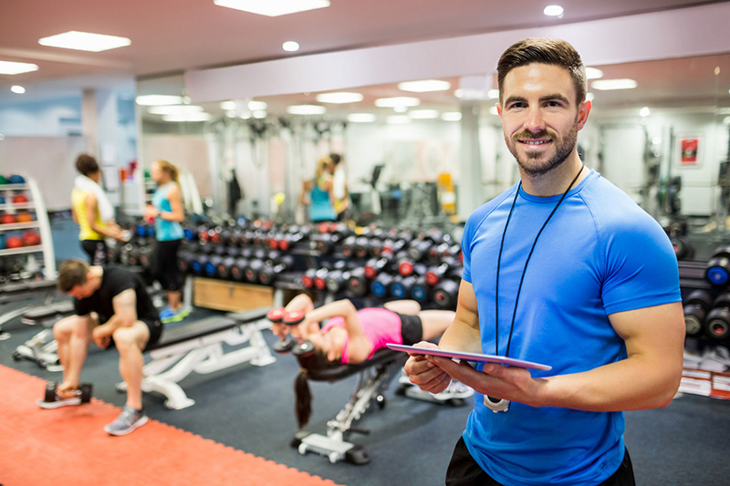 47306226 – Handsome Trainer Using Tablet In Weights Room At The Gym